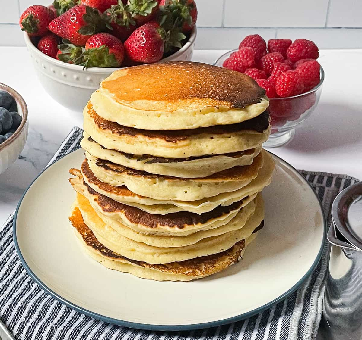 oat milk pancakes in a stack on a white plate surrounded by berries