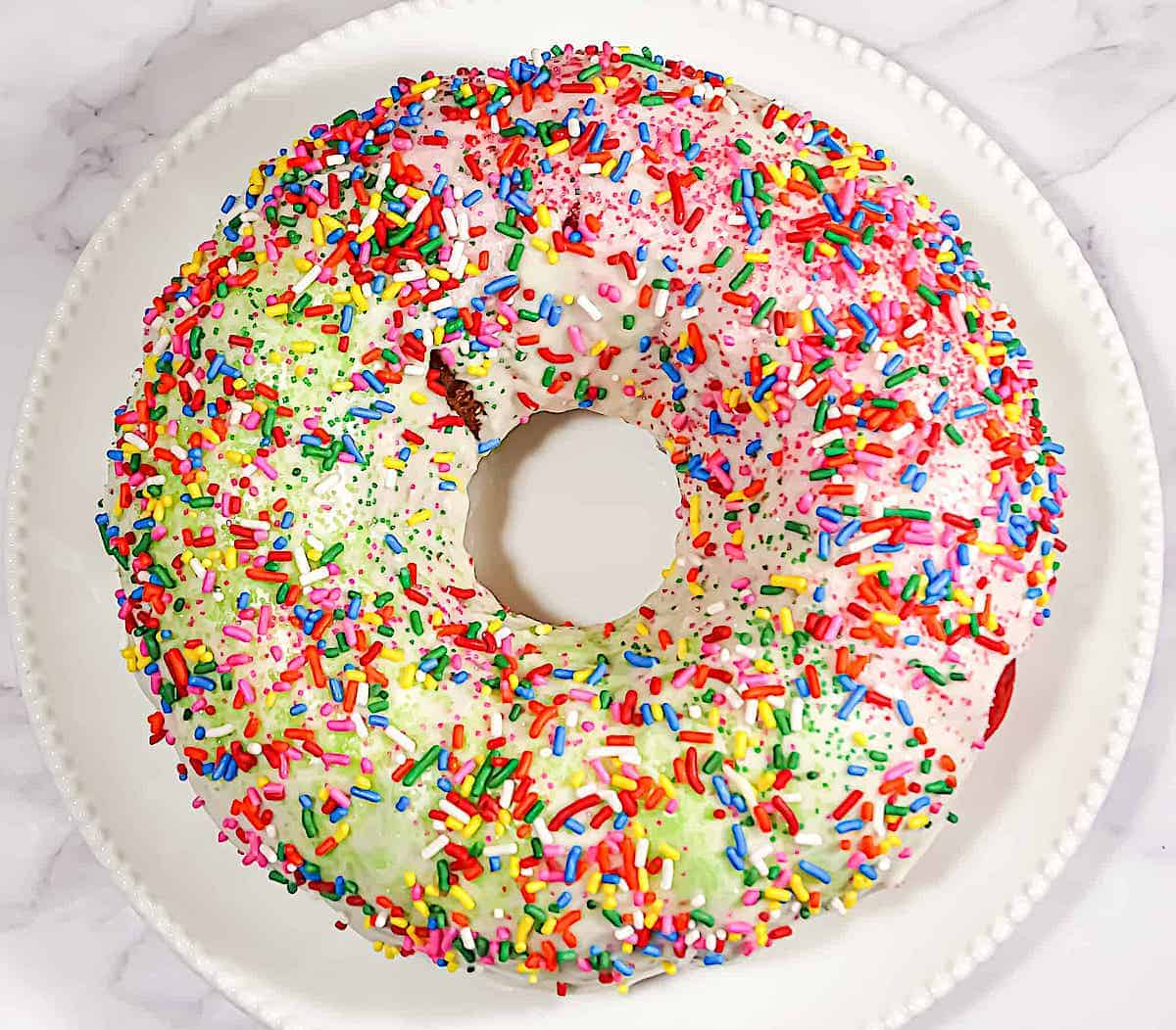 rainbow cake topped with vanilla glaze and rainbow sprinkles on a  white plate