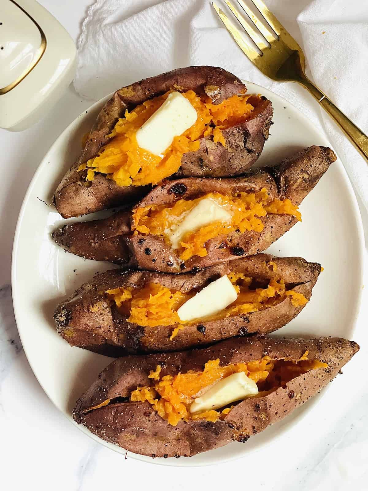 sweet potatoes on a white plate with butter topping