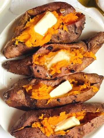 air fryer sweet potatoes on a white plate topped with butter