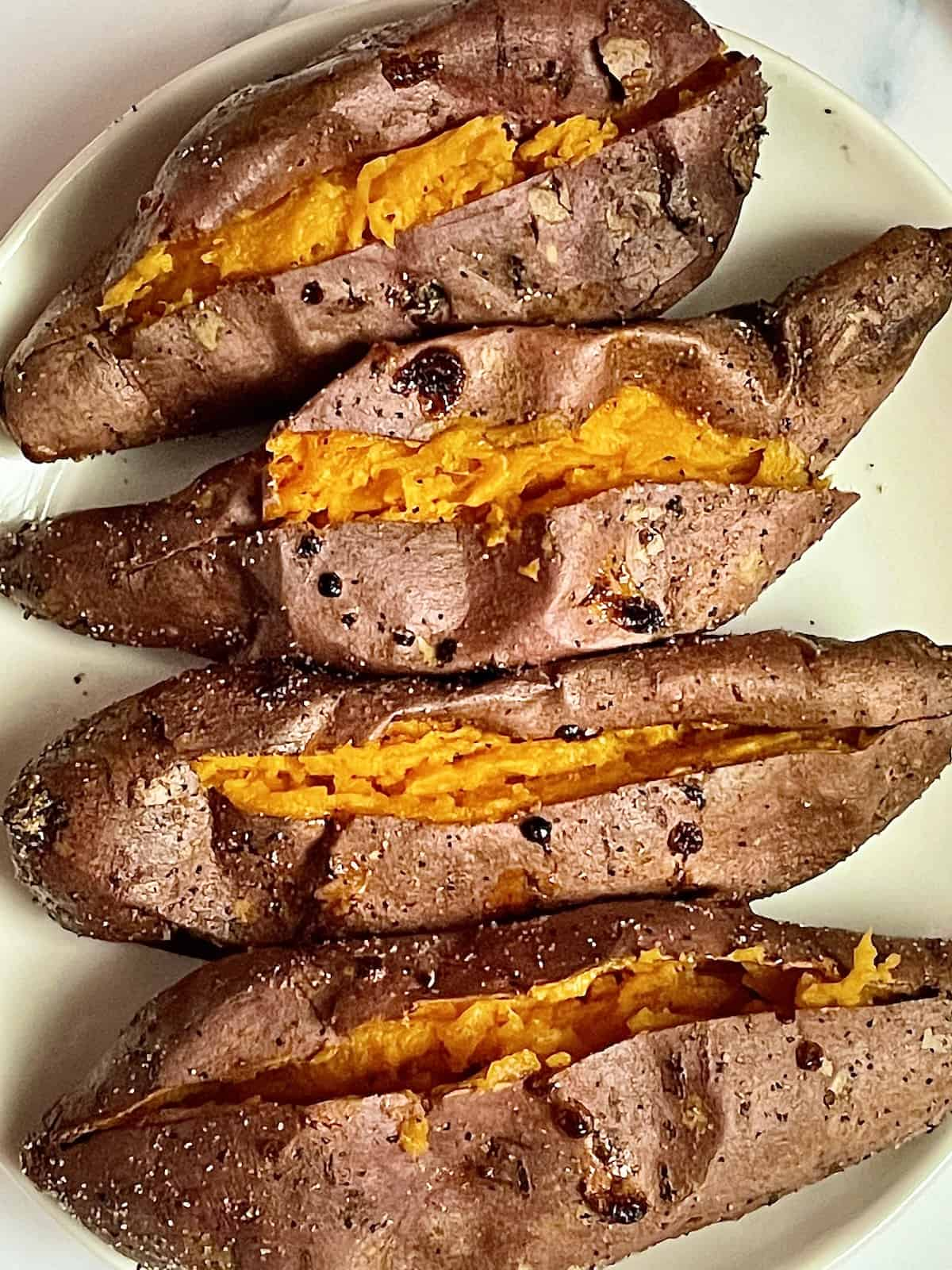 whole air fried sweet potatoes on a white plate