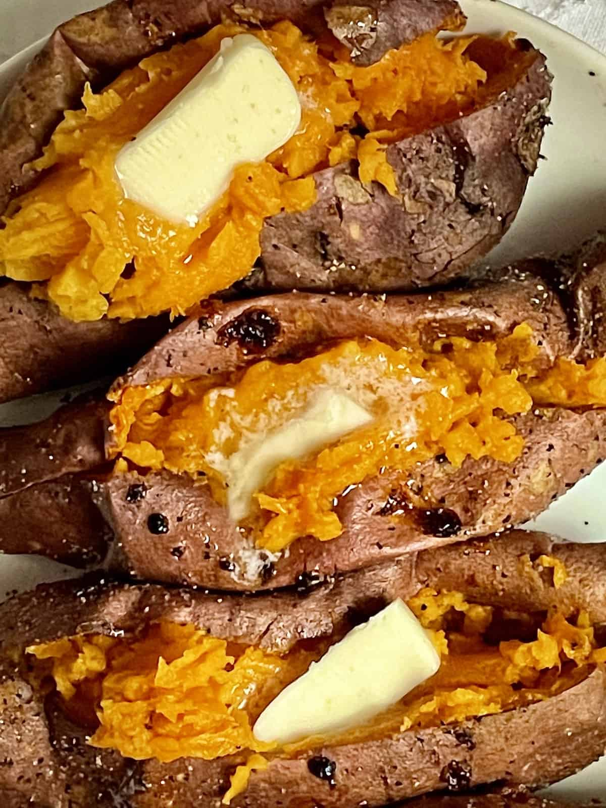 baked sweet potatoes sliced open and topped with butter
