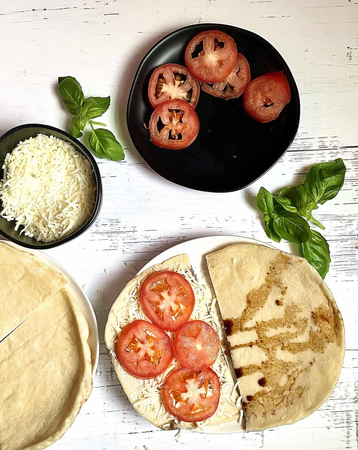 naan bread covered with mozzarella and tomatoes