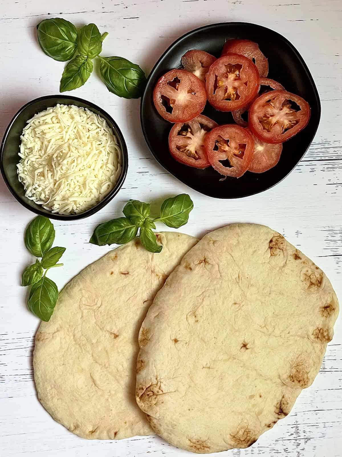 naan bread, mozzarella cheese, sliced tomatoes, and fresh basil leaves