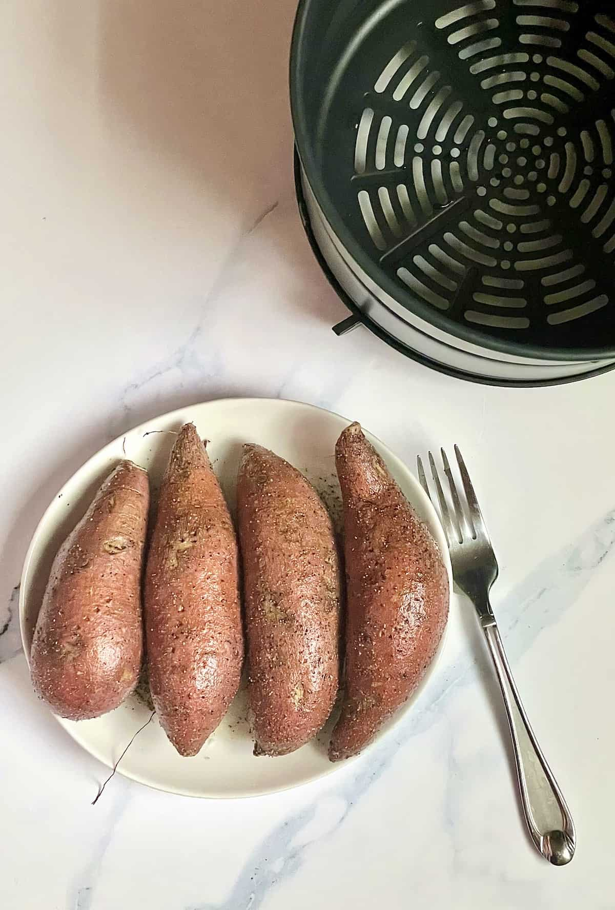 sweet potatoes on a white plate next to an air fryer