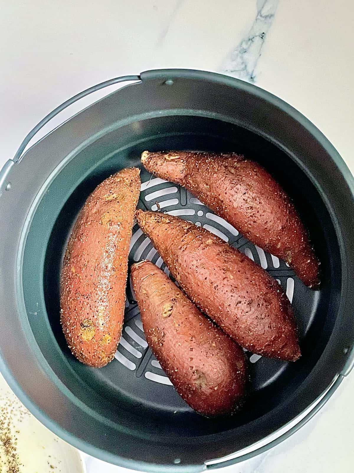 sweet potatoes in an air fryer basket rubbed with oil and salt, pepper