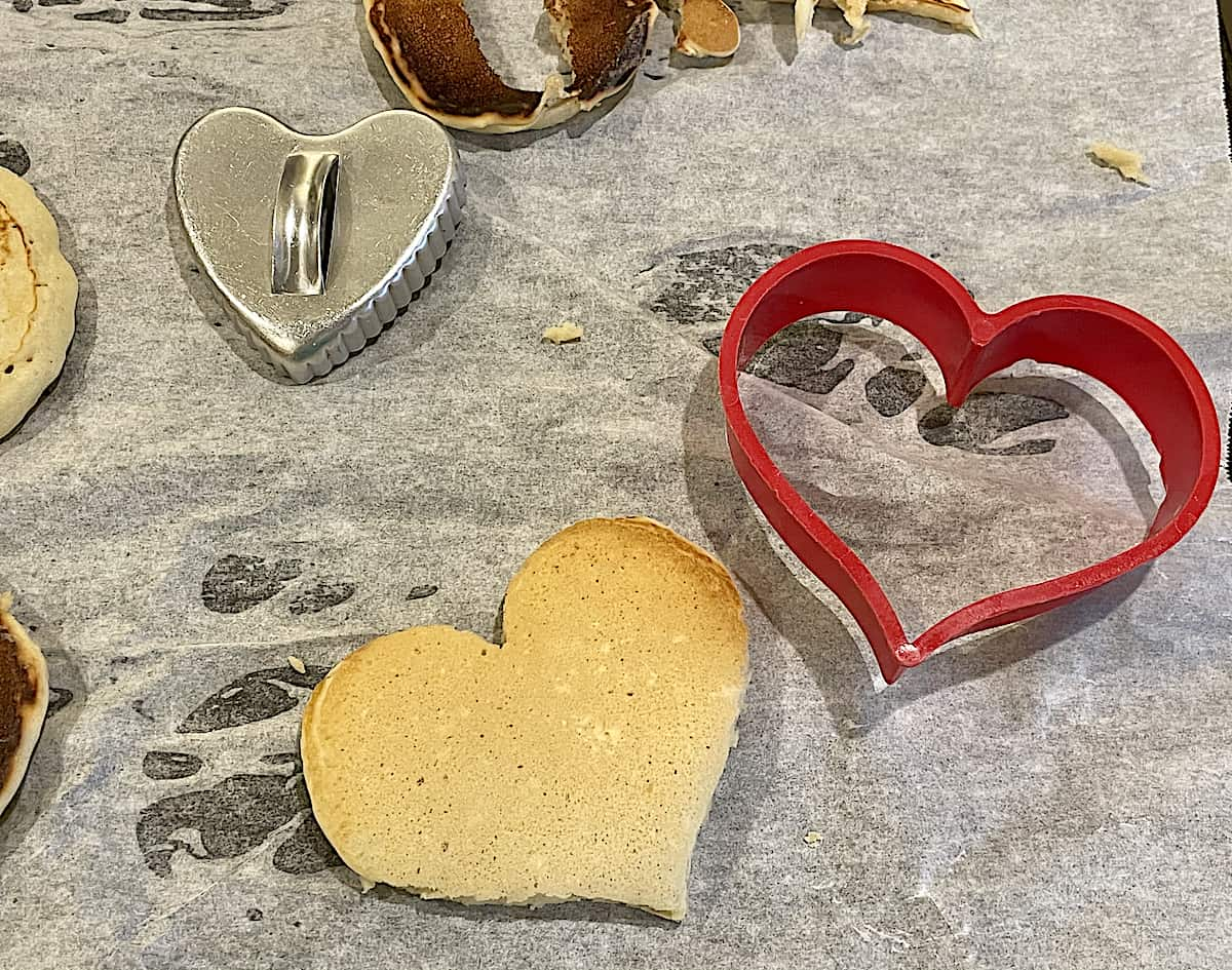 heart cookie cutters on parchment paper, cutting pancakes