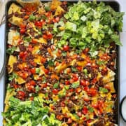loaded sheet pan nachos with lettuce and veggies on a baking sheet