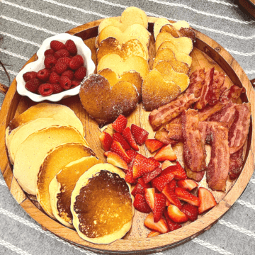a breakfast pancake board with heart pancakes, bacon, strawberries, and raspberries