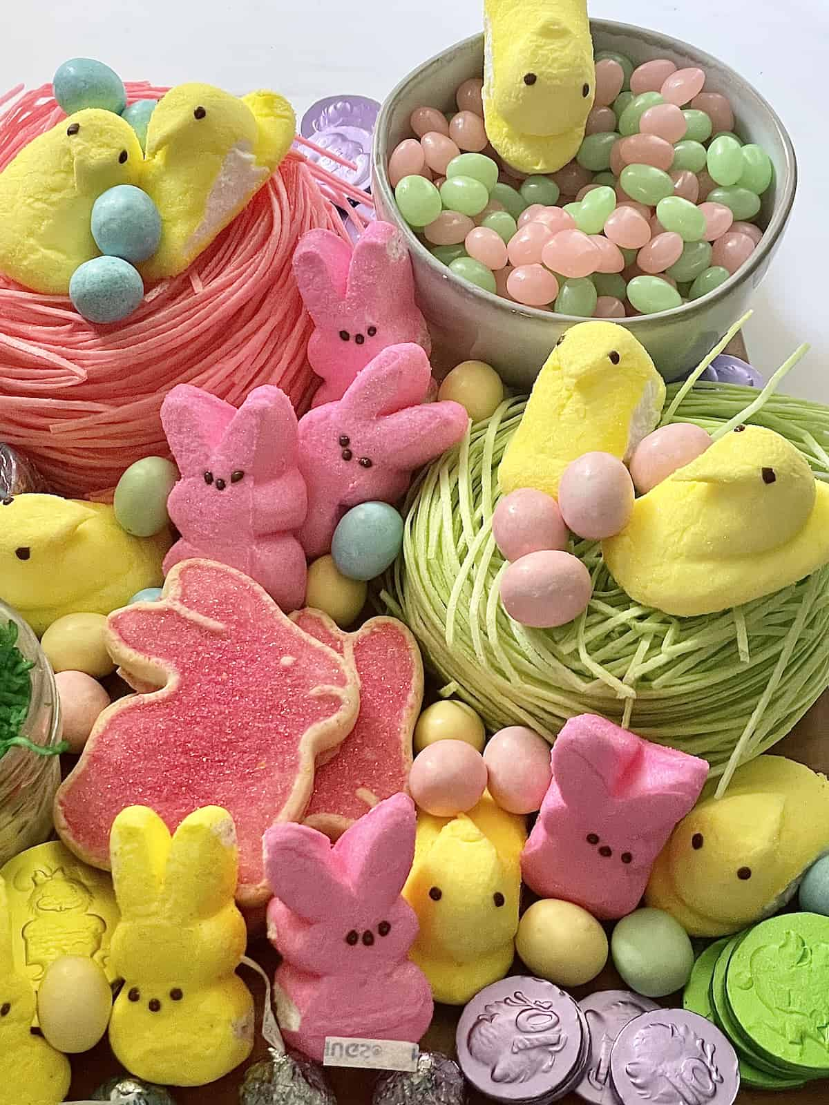birds nest, peeps, cookies, and candies on a charcuterie board