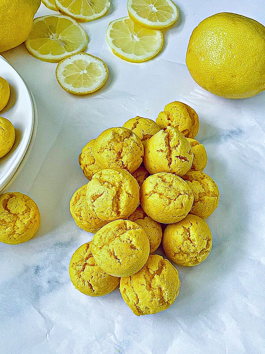 overhead image of lemon drop cookies in a pile