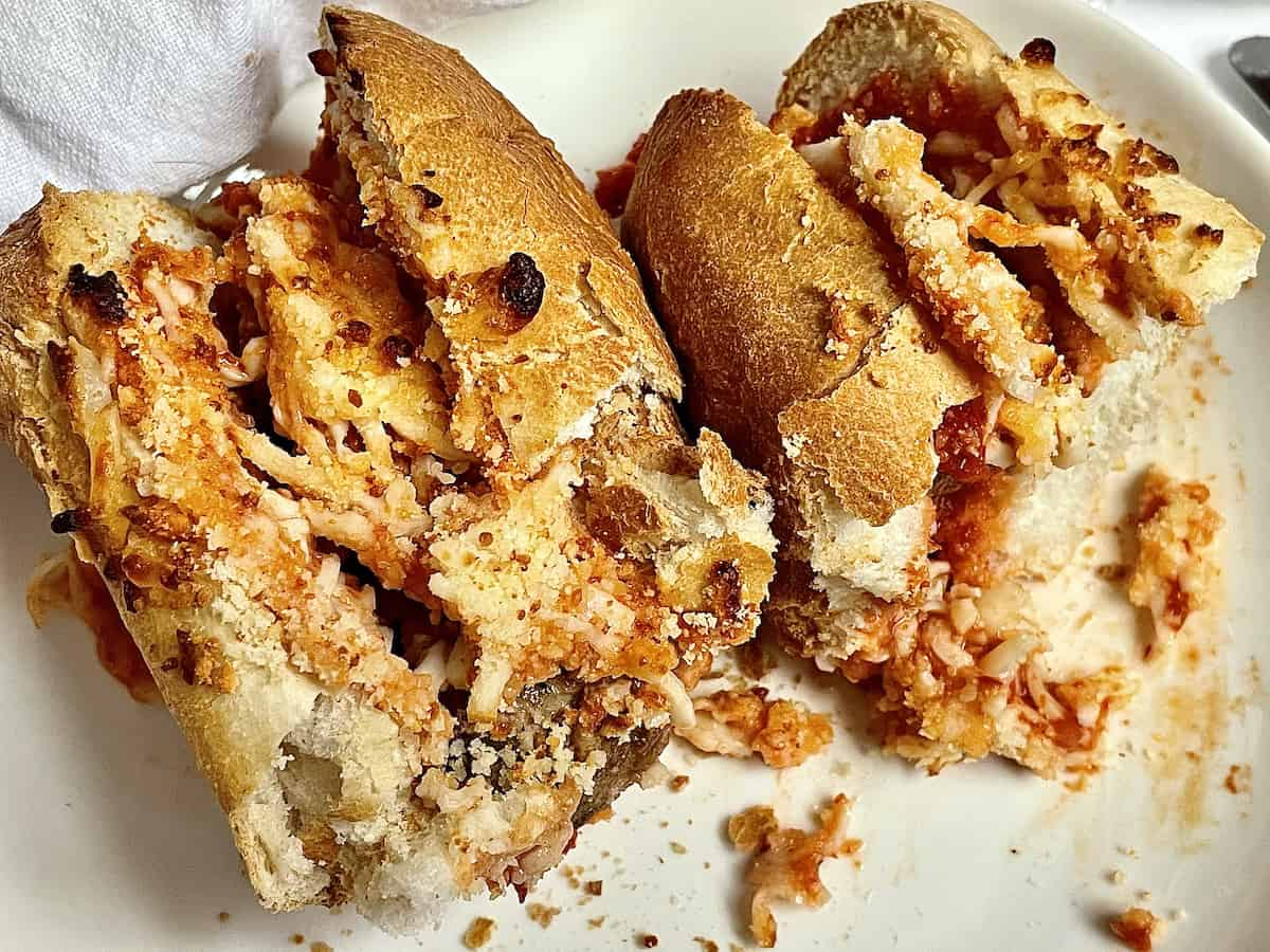 air fryer meatball parmesan sub cut into two pieces on a white plate