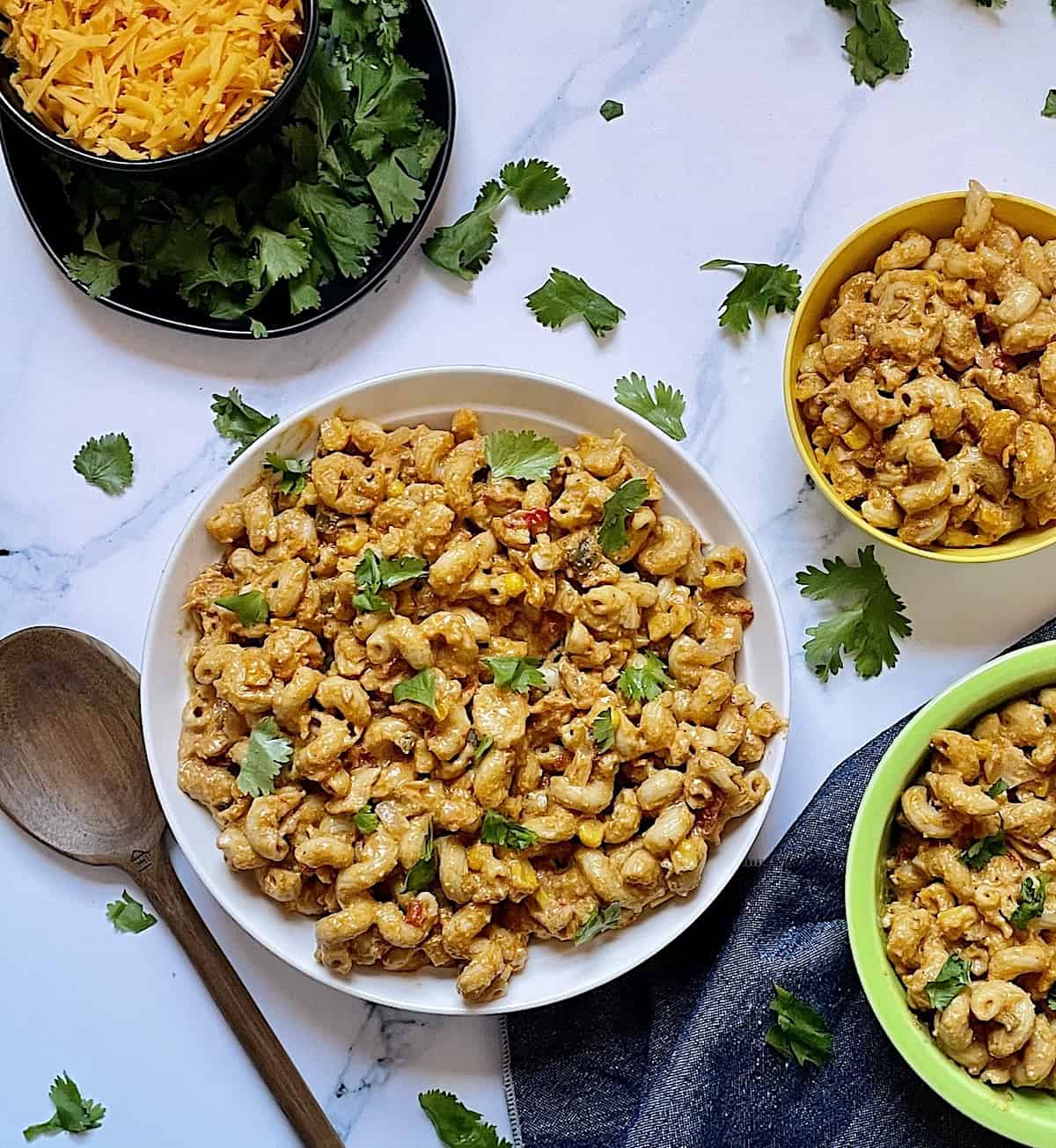 Instant Pot chicken taco pasta in 3 bowls on a white background, garnished with cilantro and cheddar cheese