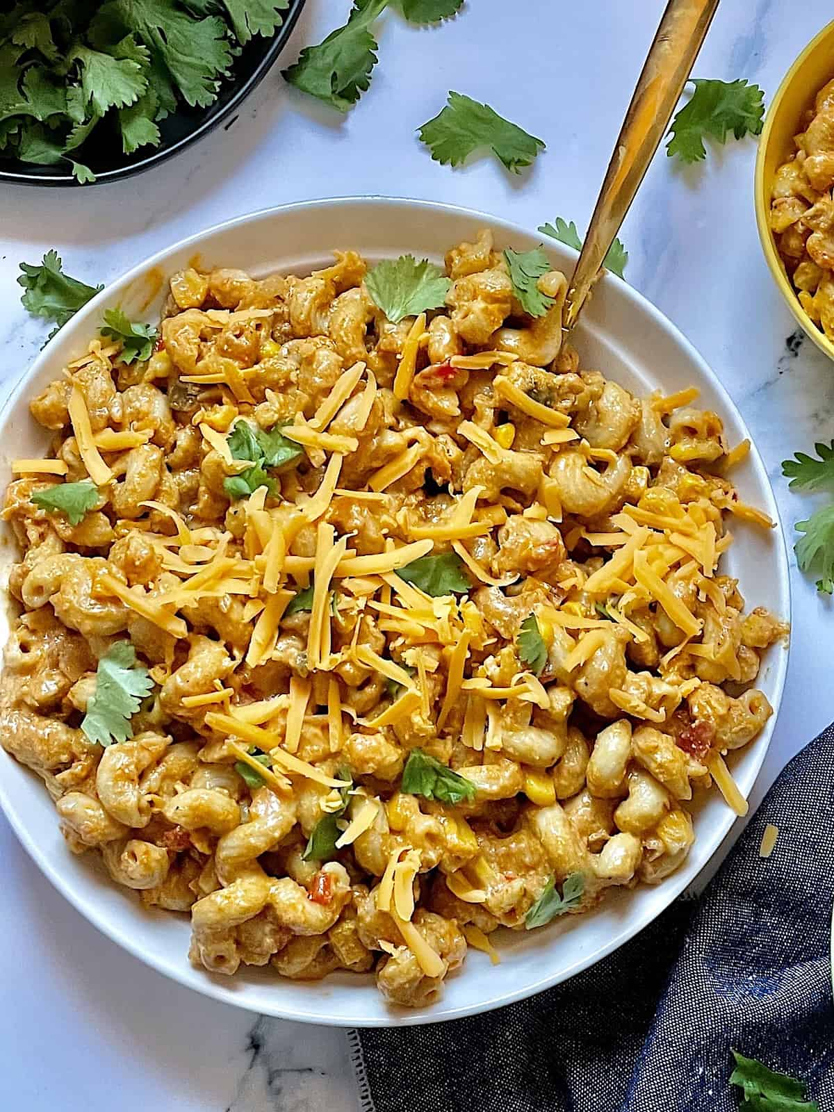 Instant Pot chicken taco pasta on a white plate topped with cilantro and cheddar cheese