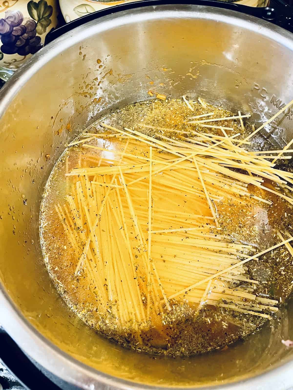 spaghetti on top of veggies with water in an instant pot