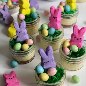 Mini Easter cheesecakes in jars decorated with coconut grass, chocolate eggs, and a bunny peep