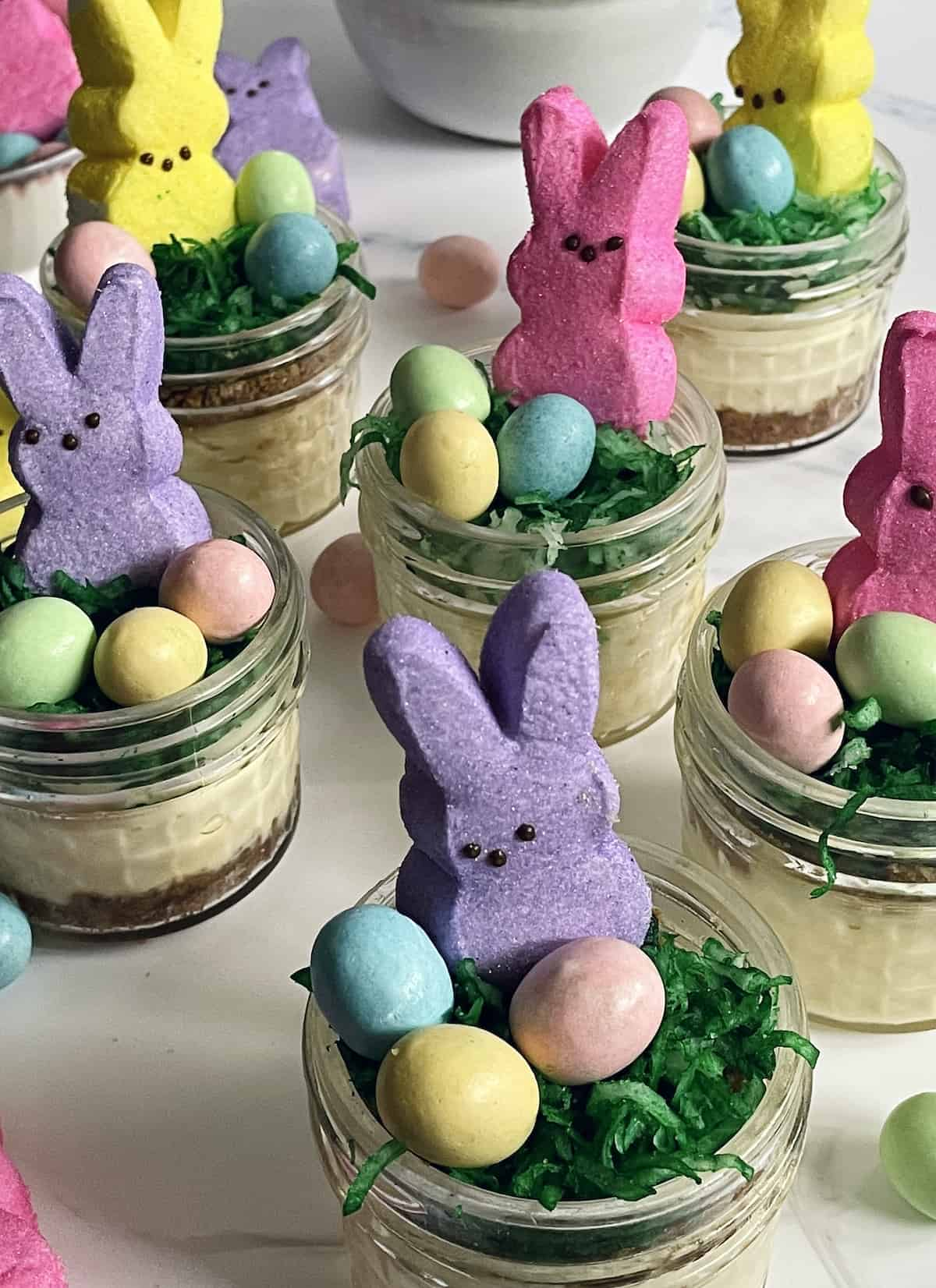 mini Easter cheesecakes in mason jars with chocolate eggs and a bunny peep