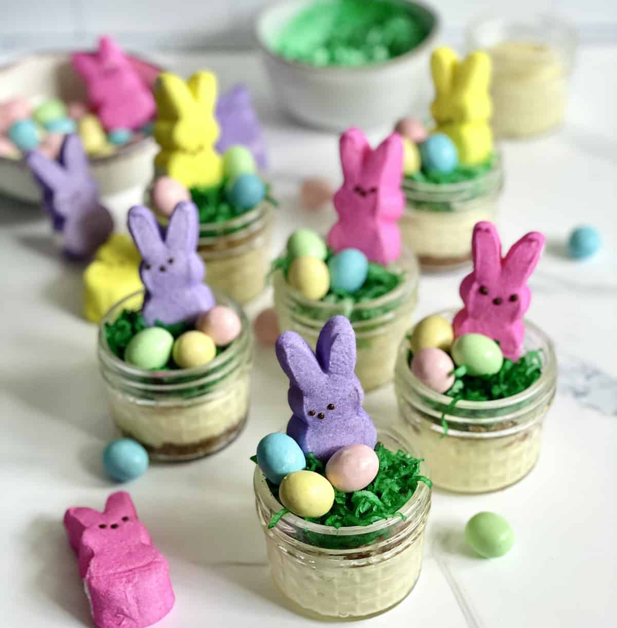Easter Bunny cheesecakes in jars with green grass, chocolate eggs, and a bunny peep