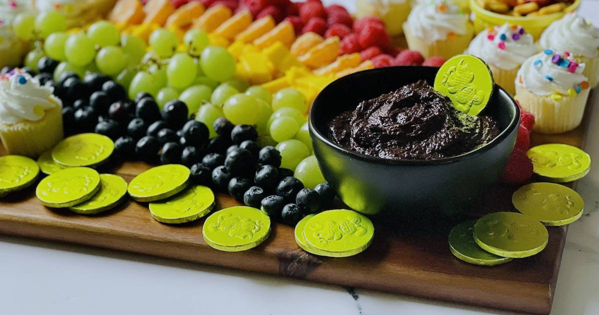close up of chocolate dip in a pot of gold on a snack board