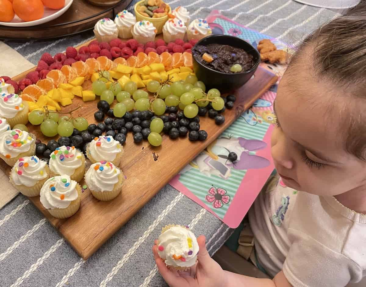 Kids eating fruit and cupcakes