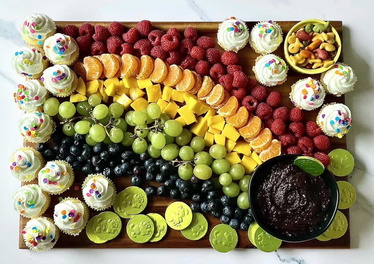 rainbow fruit board with a chocolate pot of gold and vanilla cupcakes