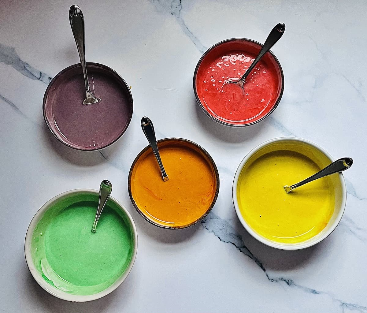 colored batter in separate bowls