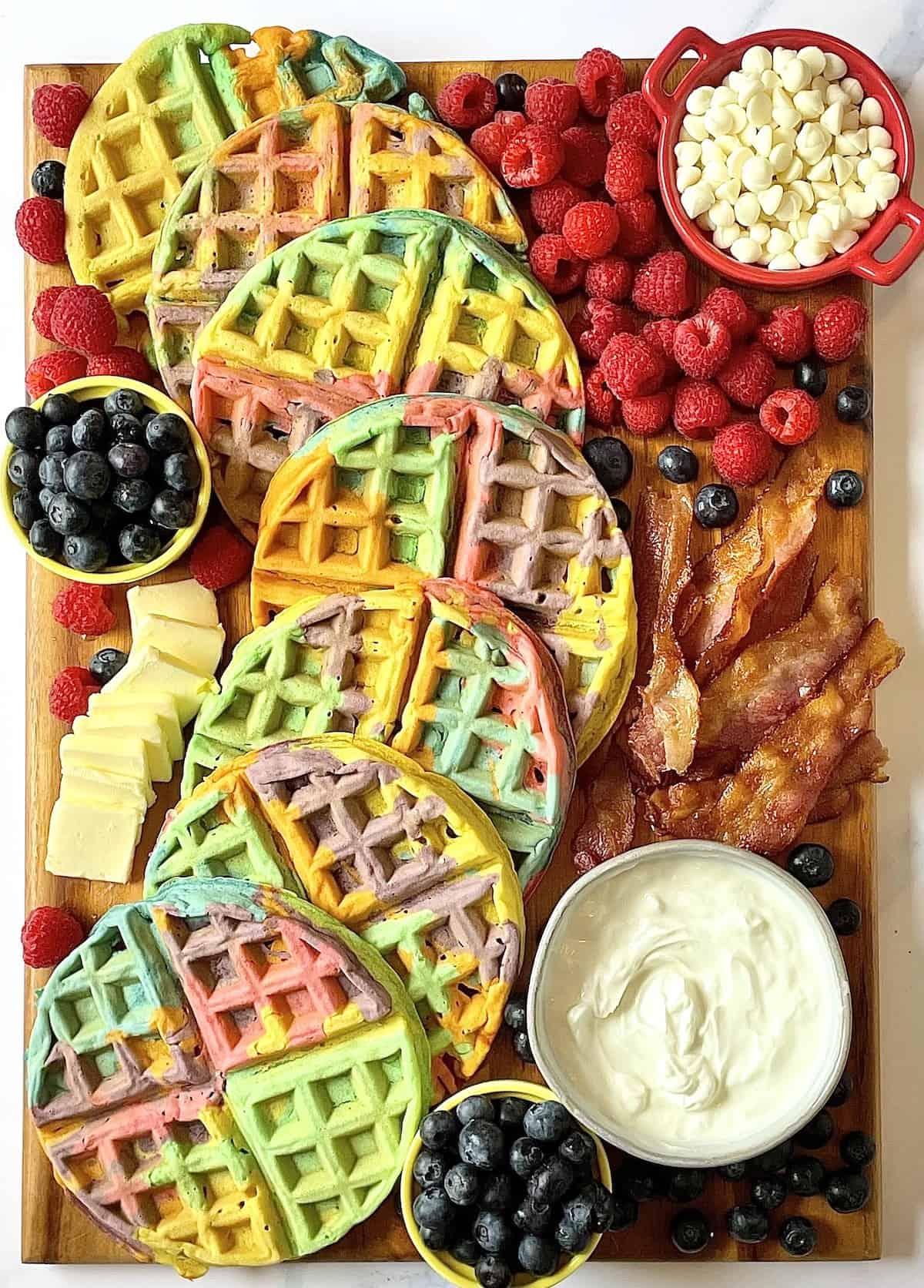 rainbow waffles, bacon, and fruit on a charcuterie board