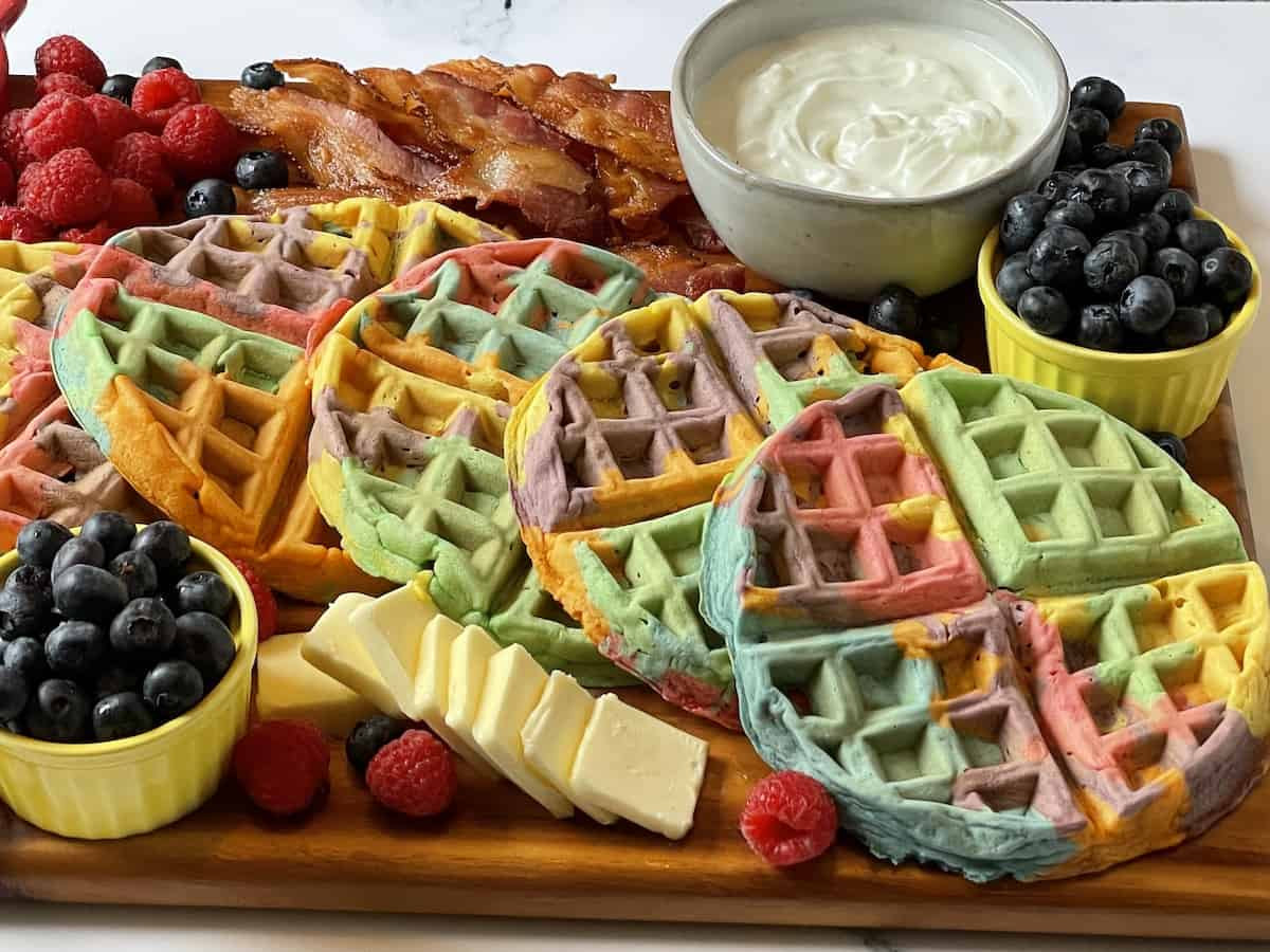 close up of rainbow waffles on a charcuterie board
