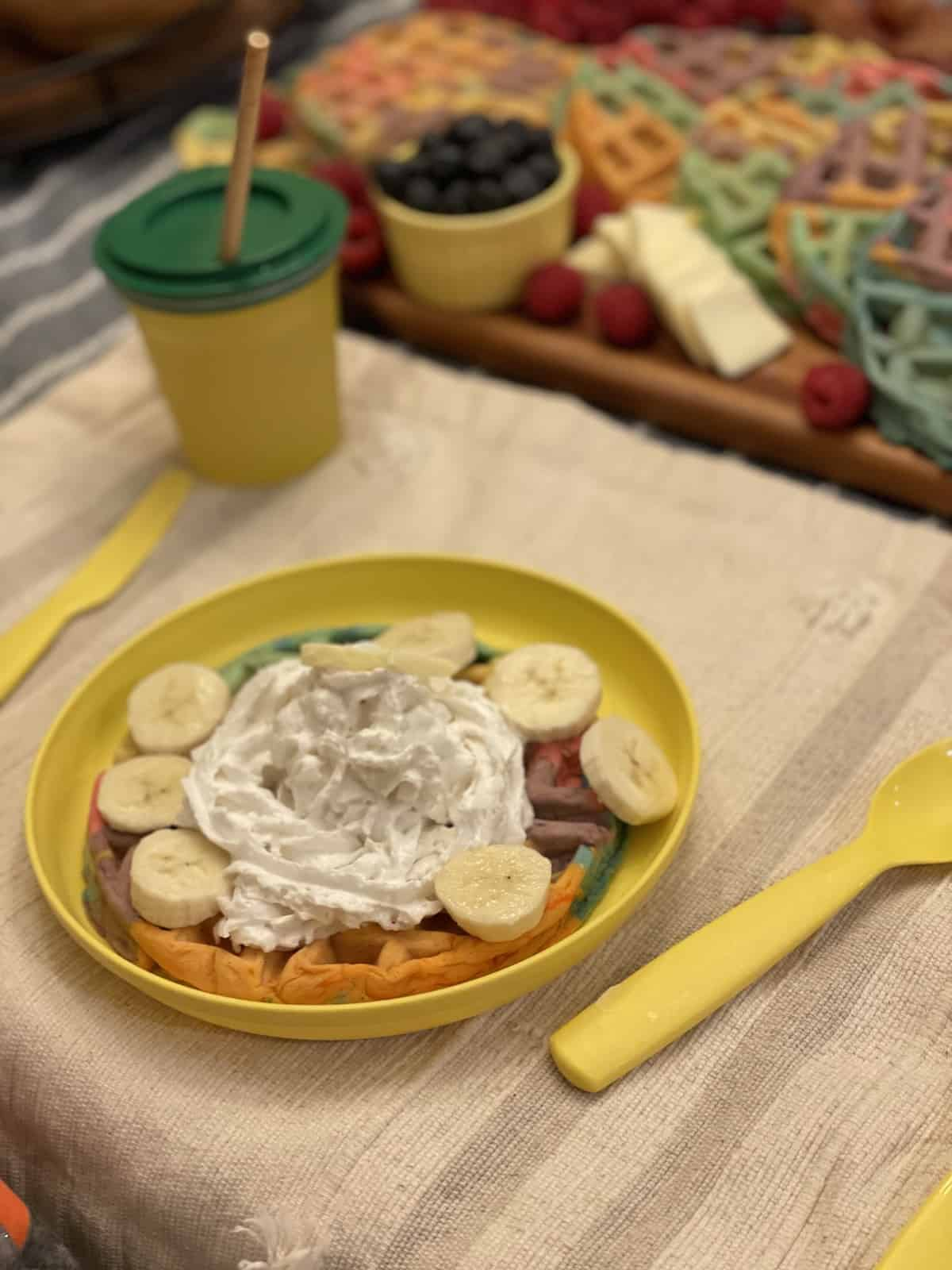 a rainbow waffle on a yellow plate with whipped cream and bananas