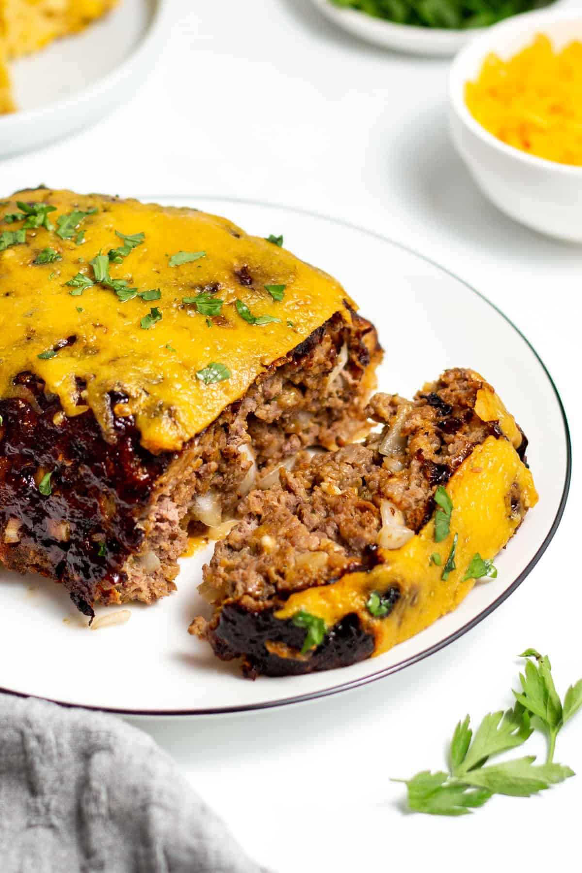 air fried meatloaf topped with cheddar cheese and herbs on a white plate
