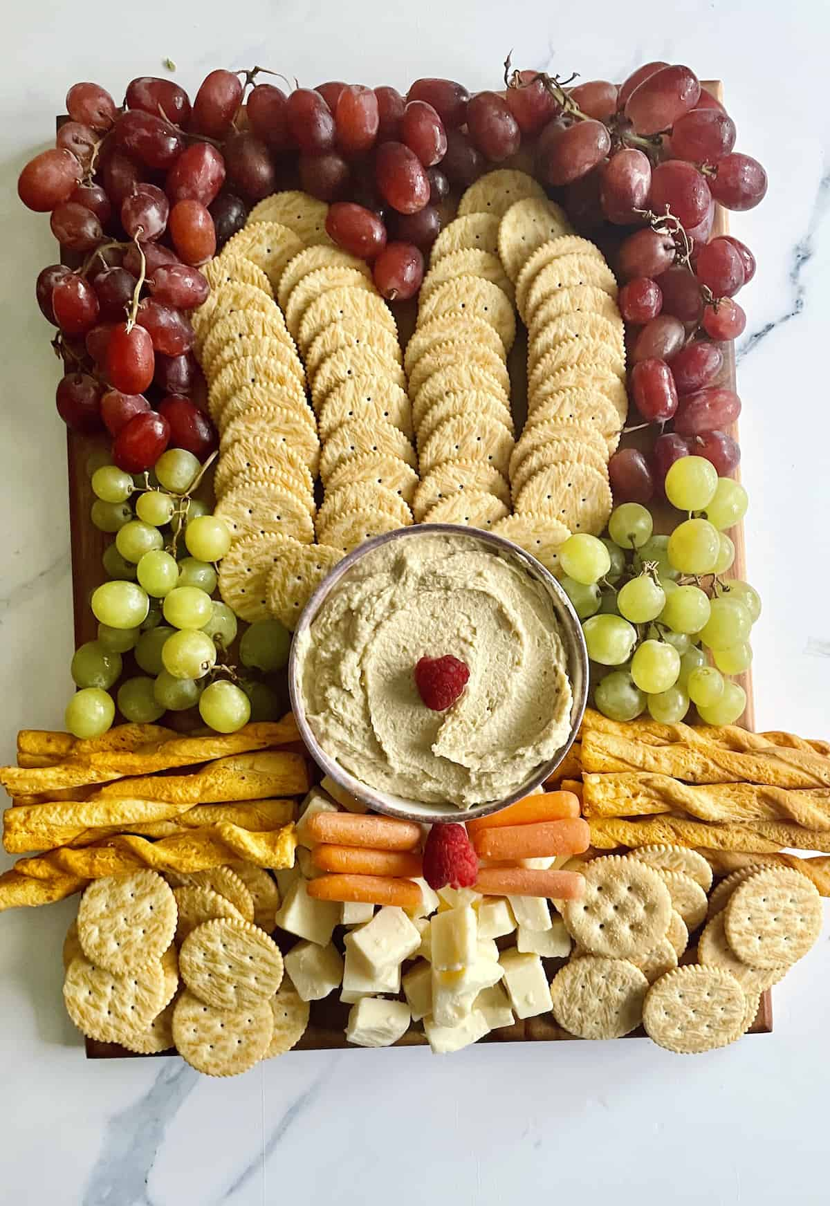 A bunny shaped fruit, veggie and cracker tray