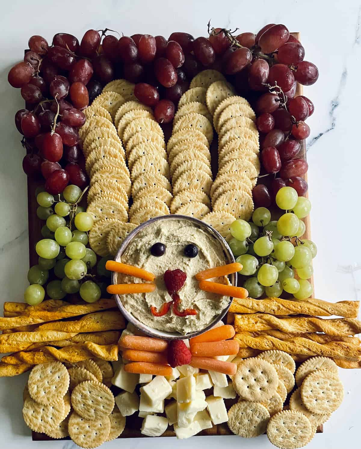 A bunny shaped fruit, cheese, and cracker tray, complete but missing the ears