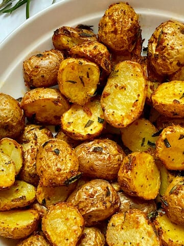 air fryer baby potatoes with rosemary and spices in a white bowl