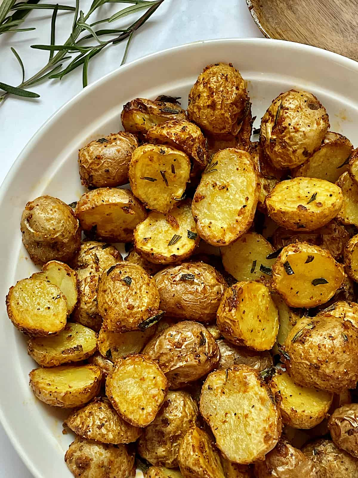 air fryer baby potatoes with spices and rosemary in a white plate