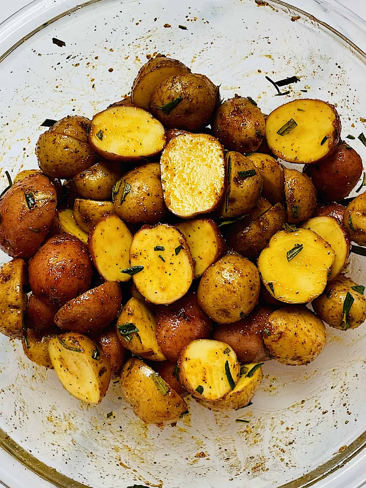 baby potatoes cut in half and mixed with oil, spices and rosemary