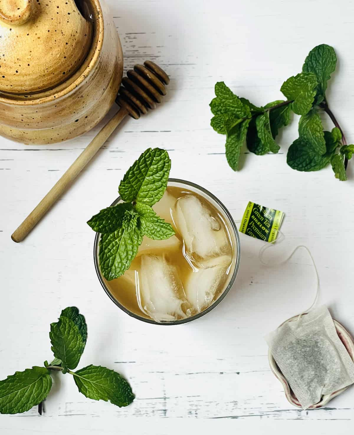 overhead shot of iced tea in a cup surrounded by mint and honey