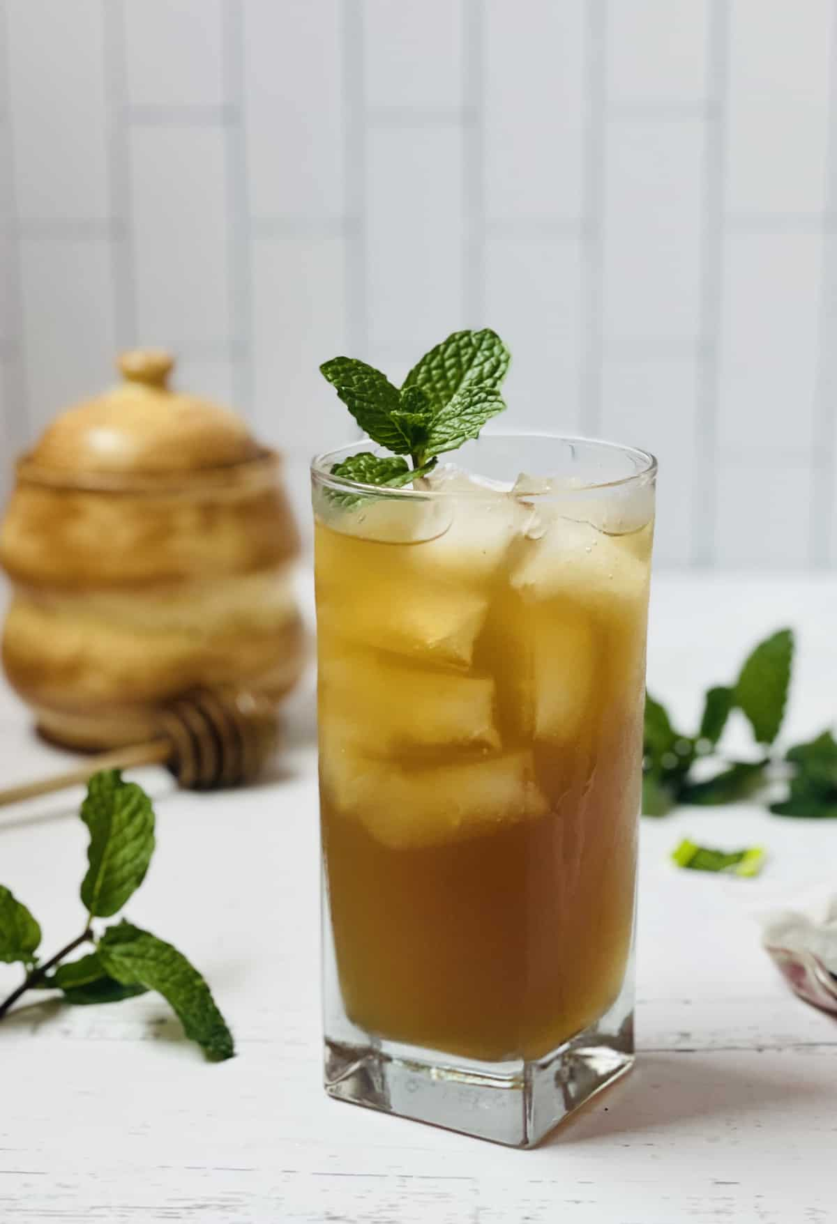 iced green tea in a cup with mint leaves and honey