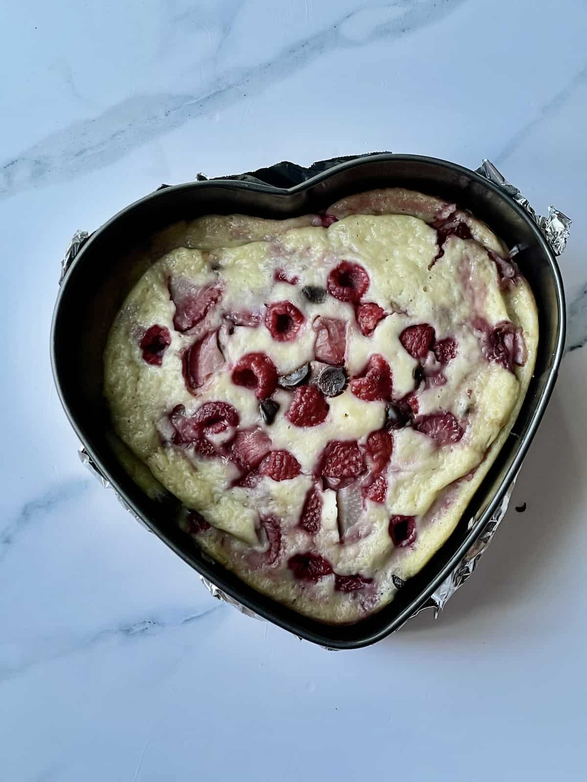 pressure cooked pancake in a heart spring form pan topped with fruit and chocolate