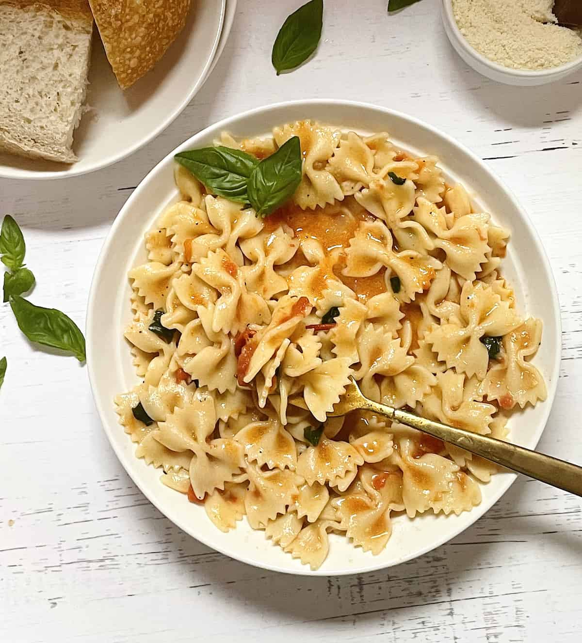 instant pot one pot pasta with bow ties, basil, tomatoes, and parmesan cheese