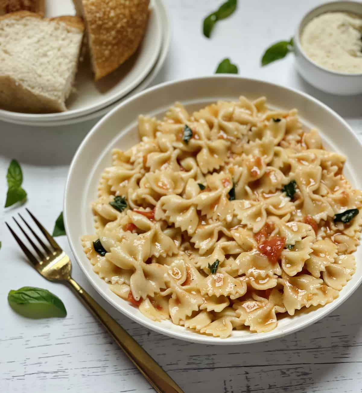farfalle pasta with tomatoes and basil on a white plate