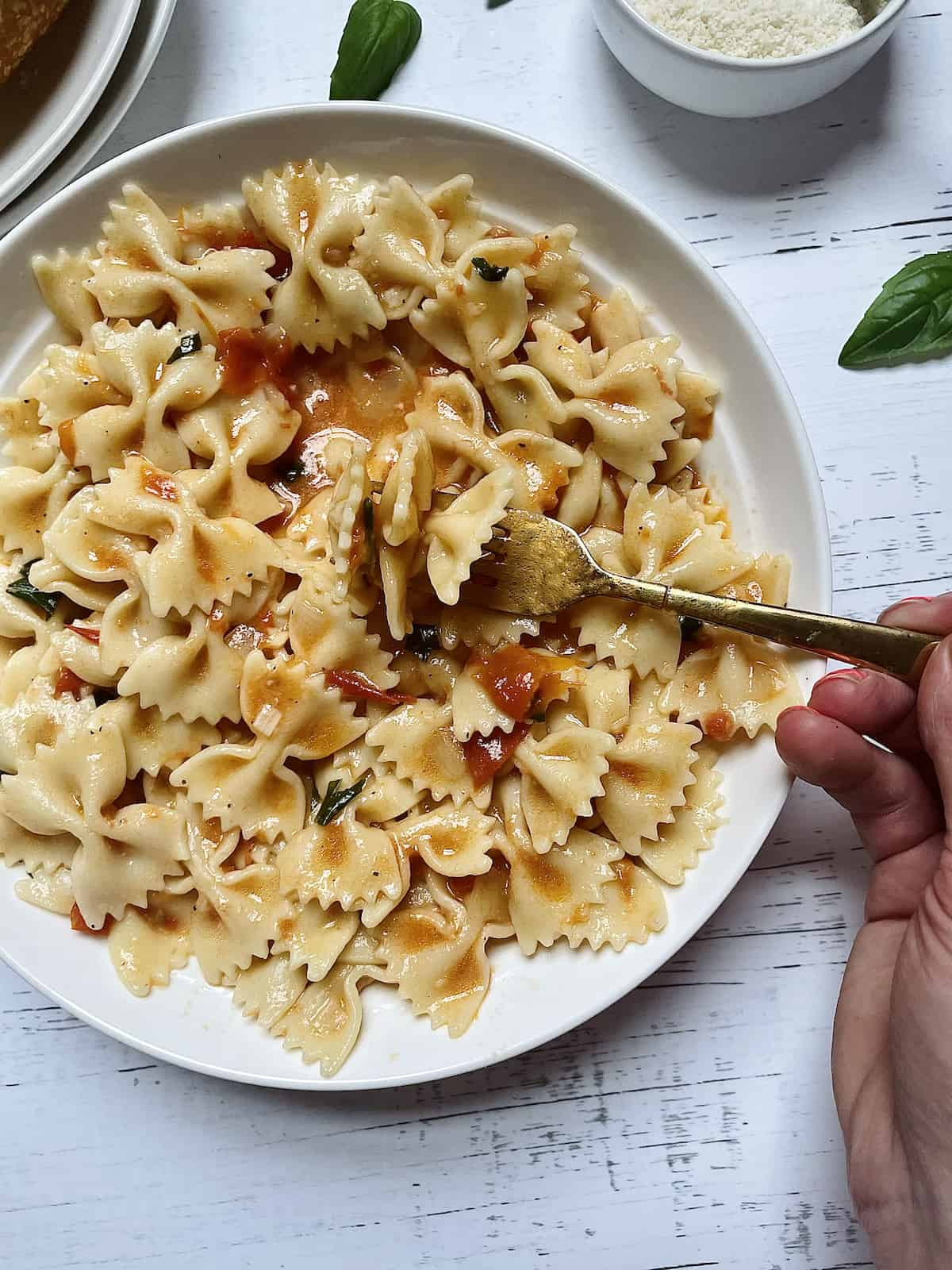 pasta with fresh tomatoes, basil and parmesan in a white plate
