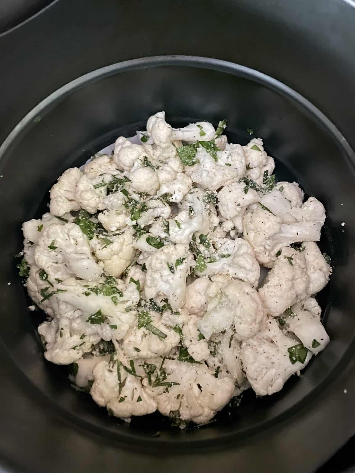 uncooked cauliflower in the basket of air fryer sprinkled with herbs and spices