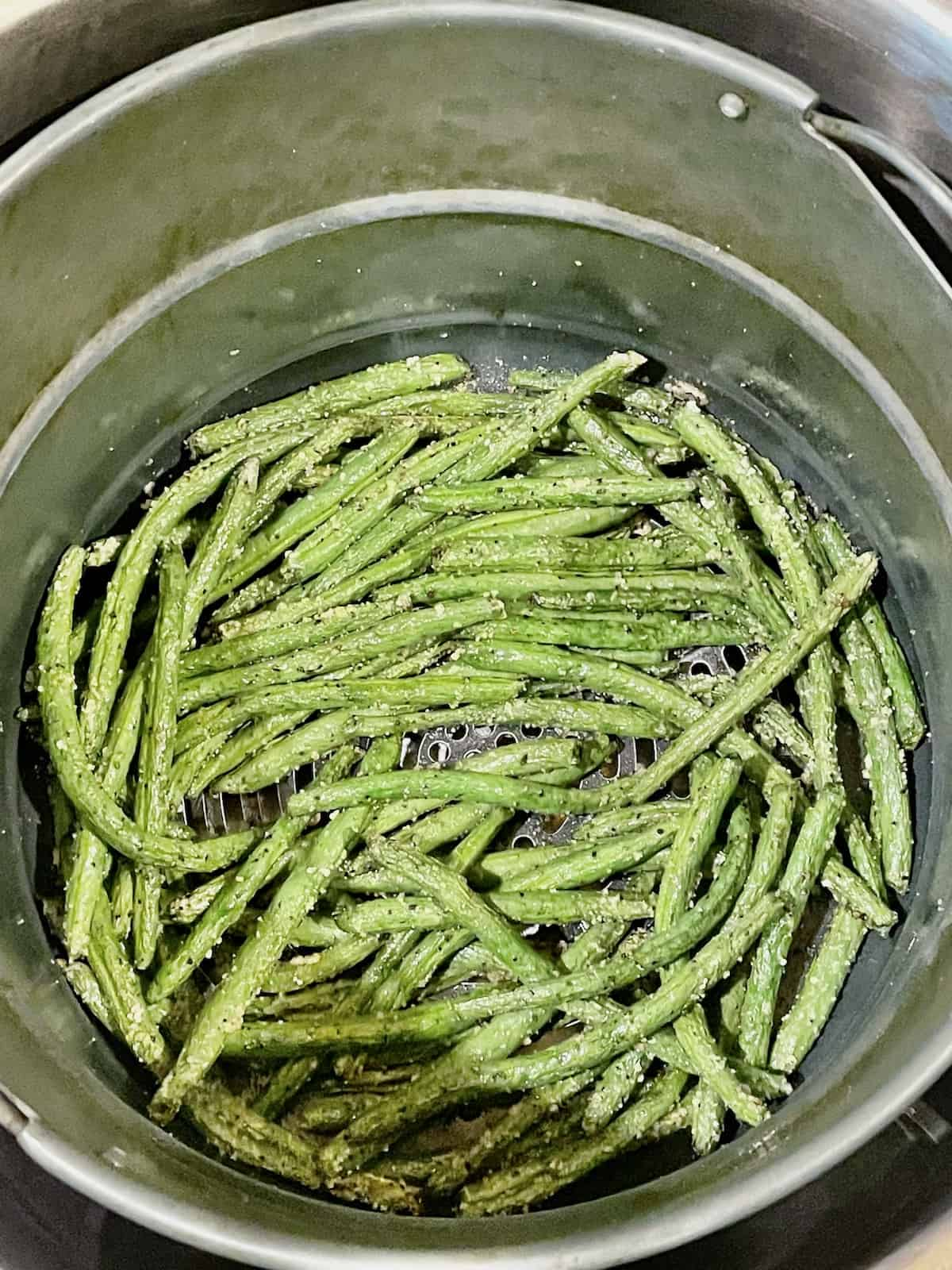 green beans in an air fryer basket tossed with salt and pepper