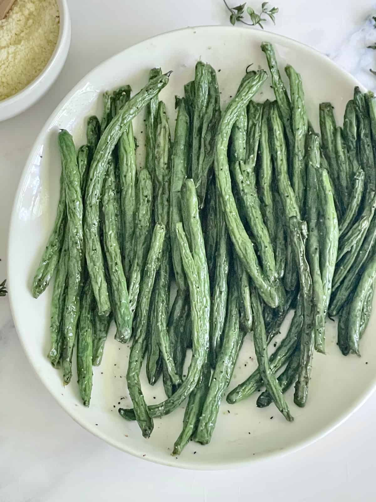 green beans on a white plate with salt and pepper