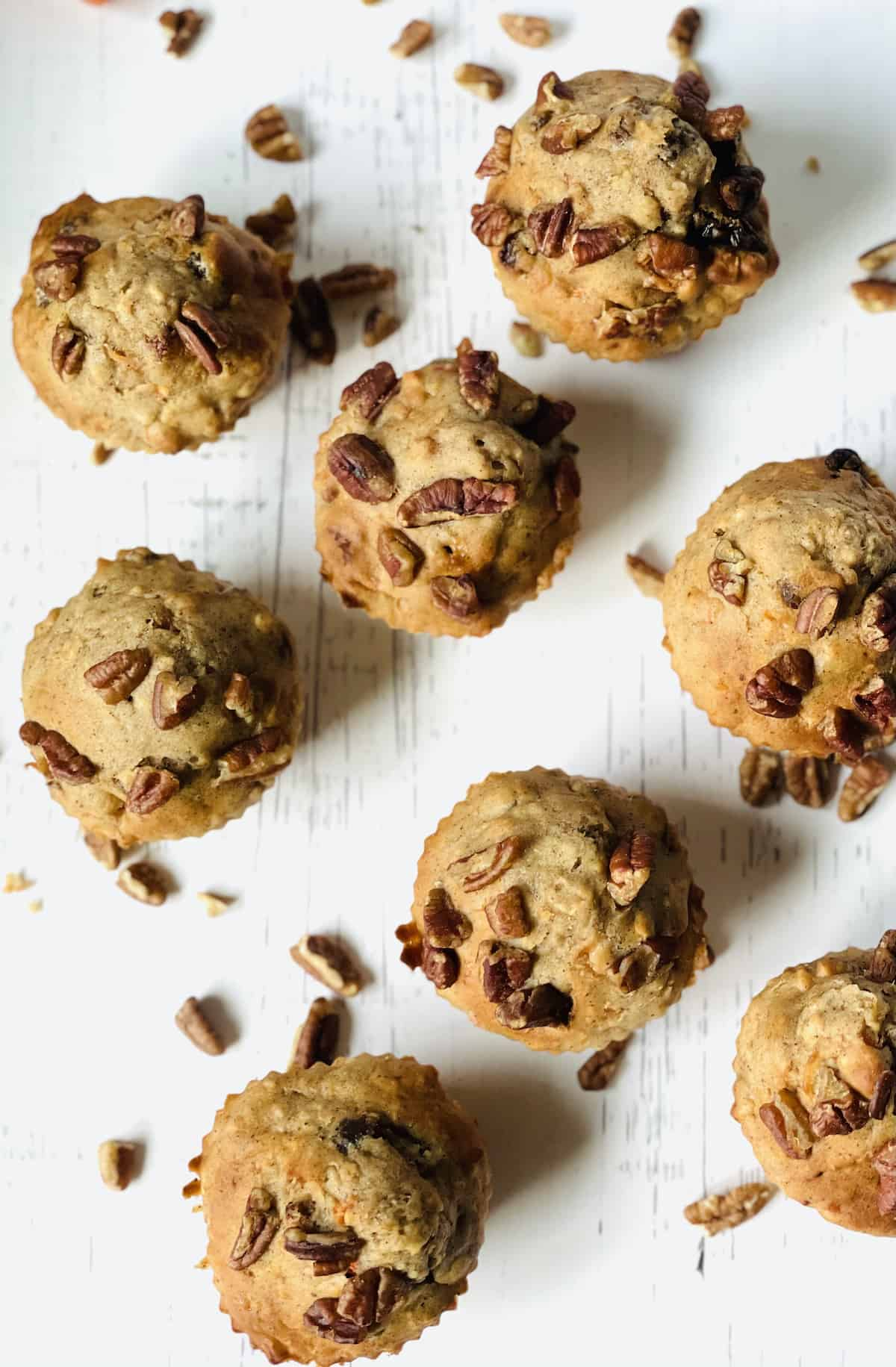 air fryer muffins on a white background topped with pecans