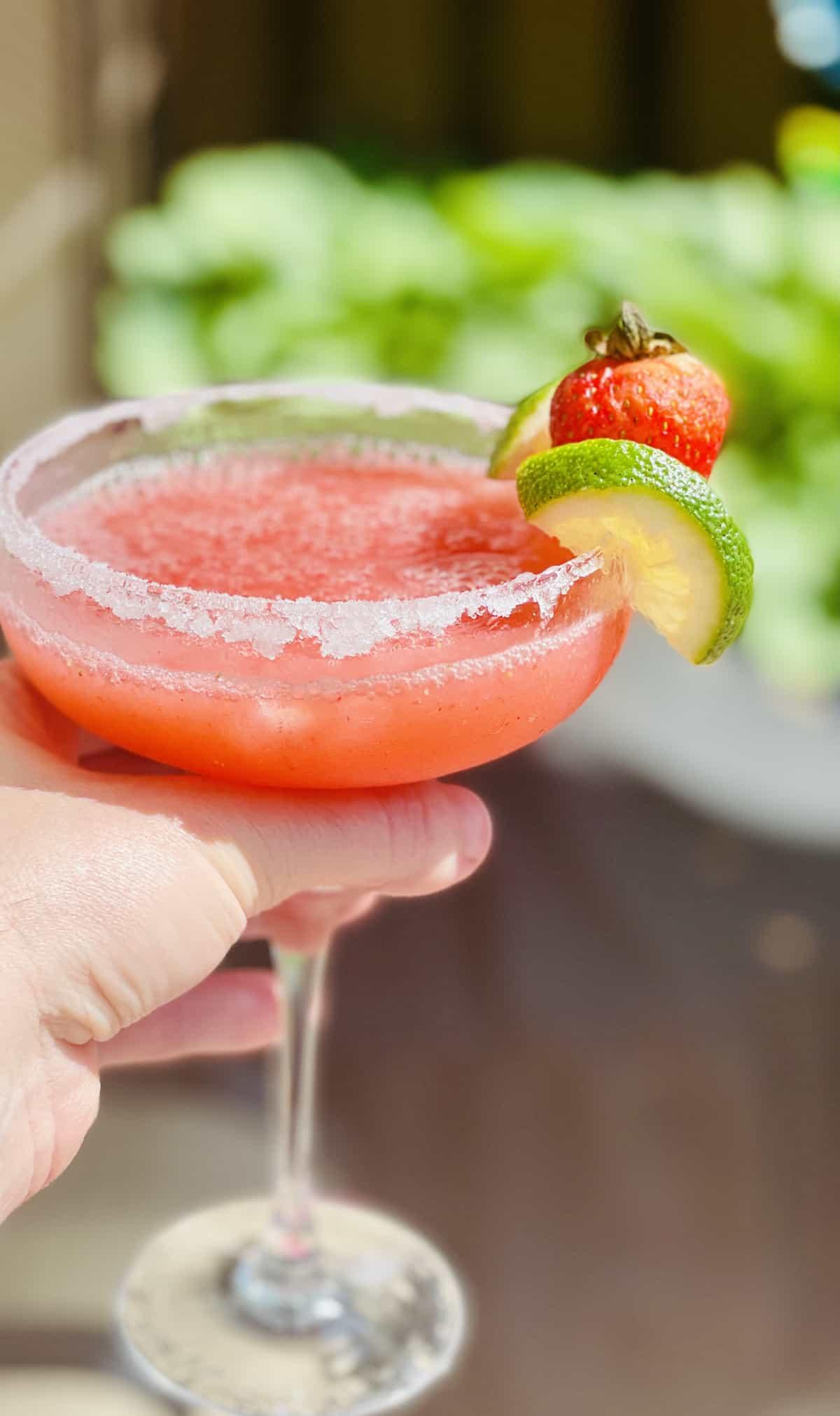 frozen strawberry margarita outside being held in a garden