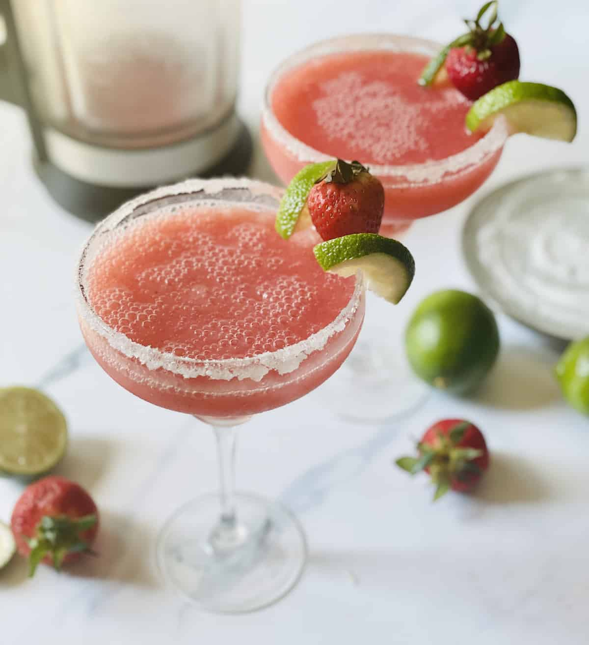 blended margaritas in glasses garnished with limes and strawberries