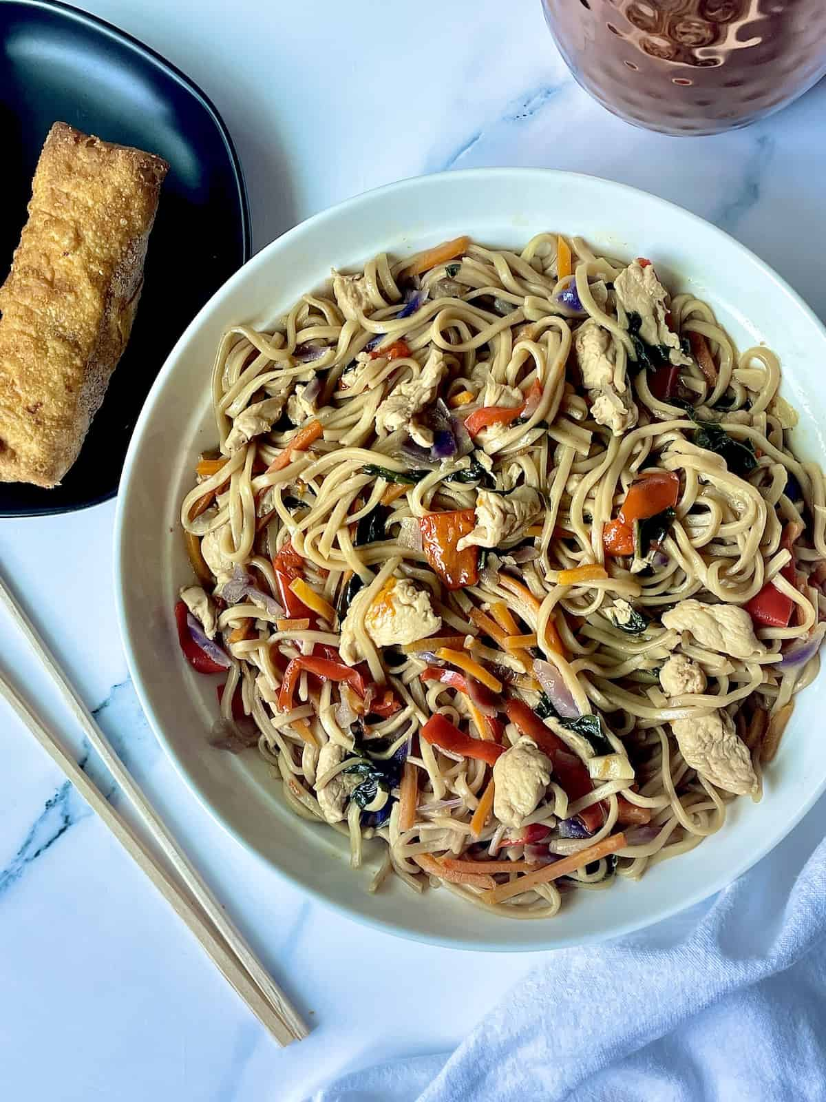instant pot chicken lo mein in a white plate with egg rolls