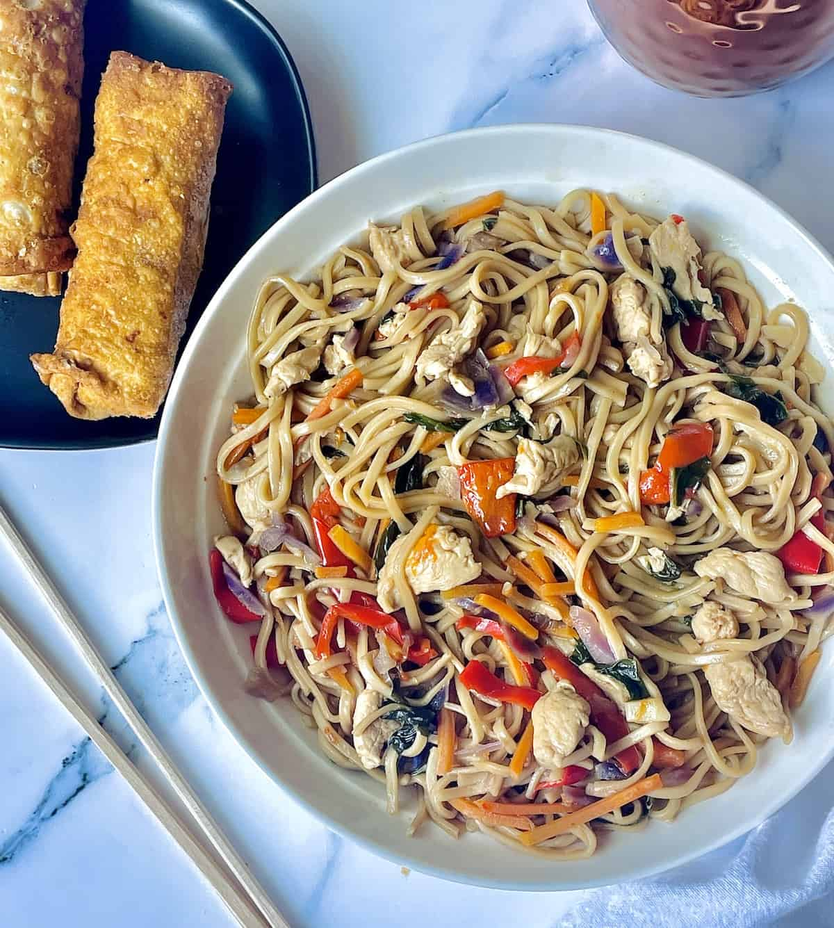 instant pot chicken lo mein in a white plate with egg rolls and chopsticks