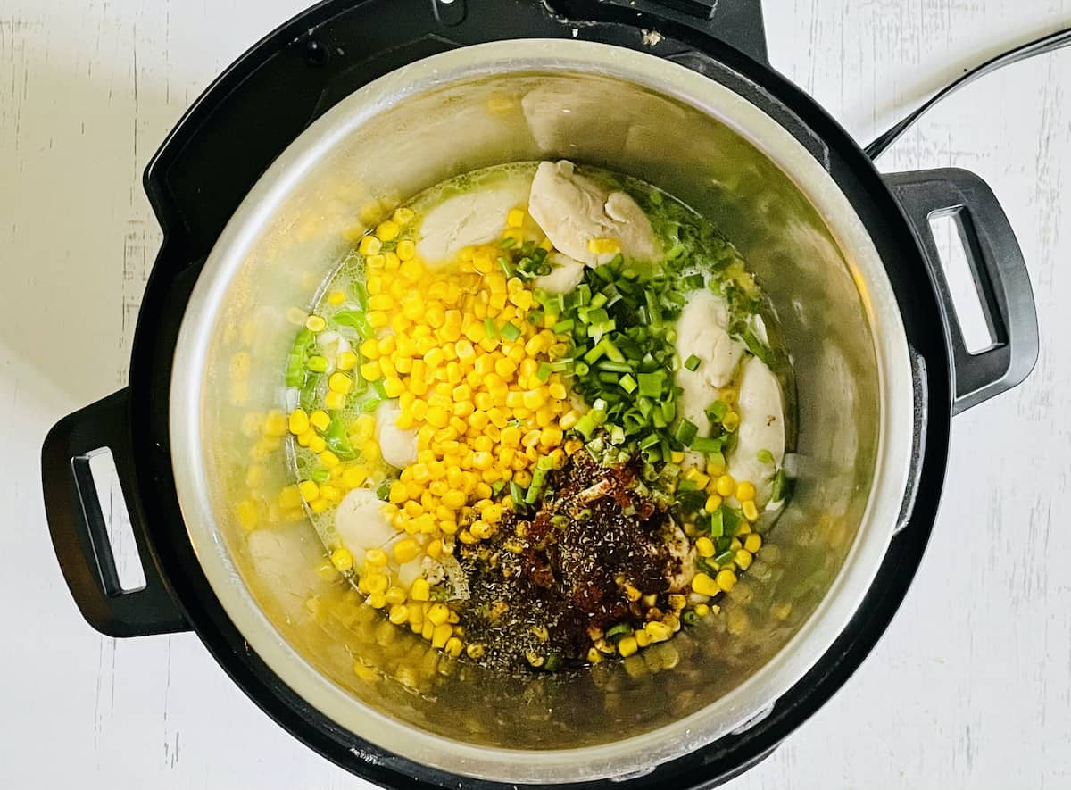 chicken, jalapenos, corn, scallions and spices in a pressure cooker